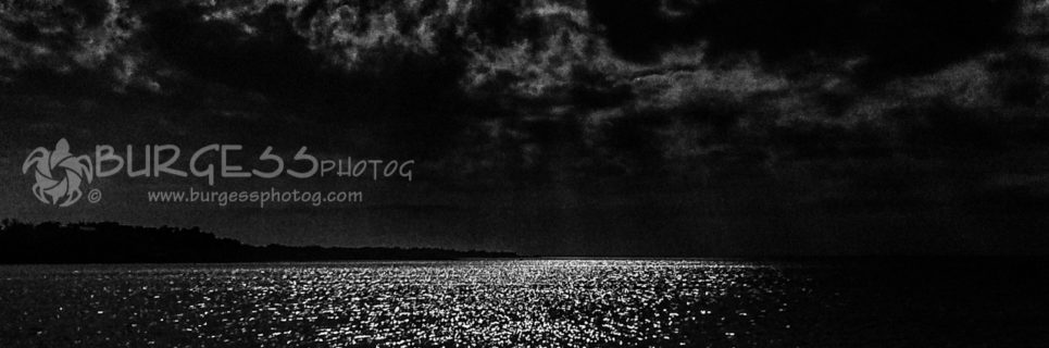 Moonshine Over the Bay; A full Moon lights up the clouds of the night sky over Santa Rosa Sound, near Pensacola, Florida; shimmering clouds and water reflections; black and white photo by Charles Burgess of BURGESS photog; www.burgessphotog.com; All Rights Reserved